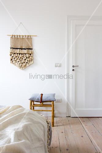 Schlafzimmer mit Holzdielenboden, Handarbeit an weißer Wand