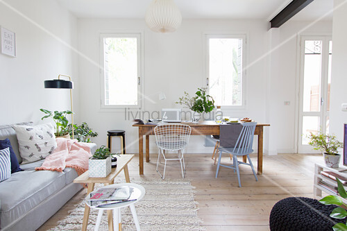 Graues Sofa und alter Holztisch mit Stühlen in offenem Wohnraum mit weißen Wänden