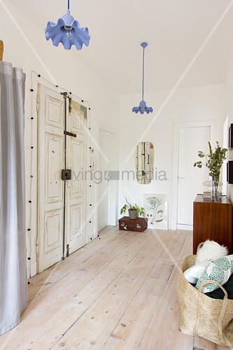 Vintage front door in white foyer with wooden floorboards