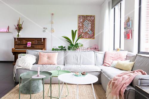 Hellgraues Sofa und pastellfarbene Deko im Wohnzimmer mit Klavier