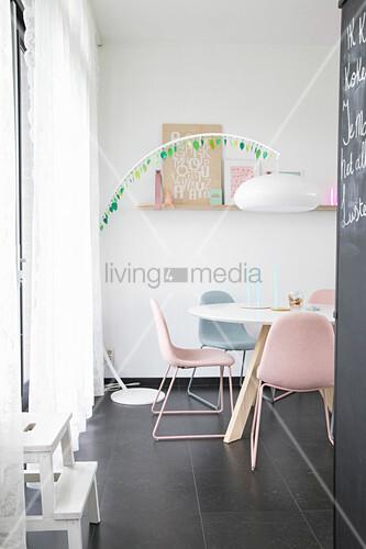 Bogenleuchte überm Esstisch mit pastellfarbenen Polsterstühlen