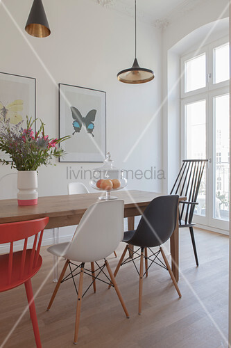 Various designer chairs around dining table next to period window