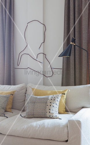 Contour of person made from cables decorating wall above sofa