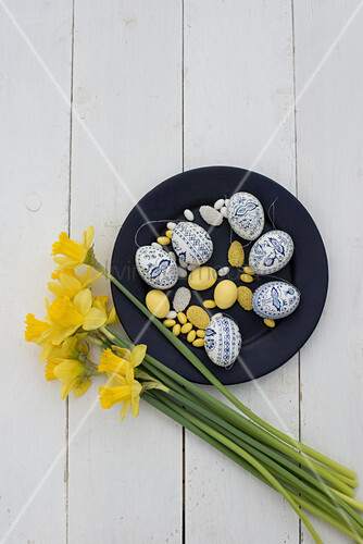 Easter eggs painted blue and white, yellow sugar eggs and marzipan eggs on plate next to narcissus