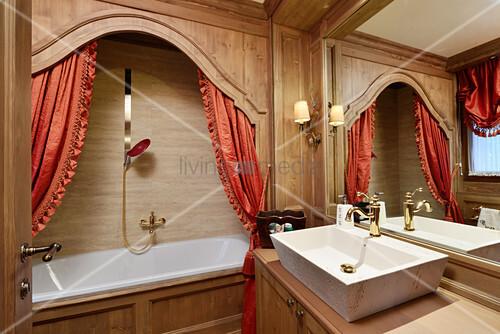 Opulent bathroom with red curtains on bathtub