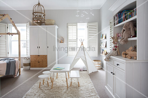 White furniture and teepee in bright child's bedroom