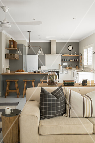 Scatter cushions on pale sofa bed, tree stump side table and kitchen with counter and grey wall in background in open-plan interior