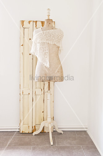 Tailors' dummy wearing crocheted shawl in front of old door leaf