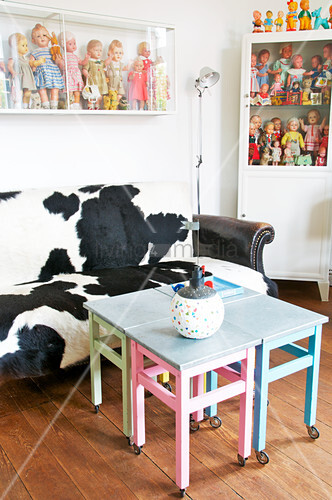Cowhide sofa, four stools used as coffee table and collection of dolls on shelves
