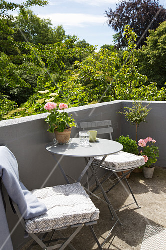 Folding furniture on sunny balcony with masonry balustrade