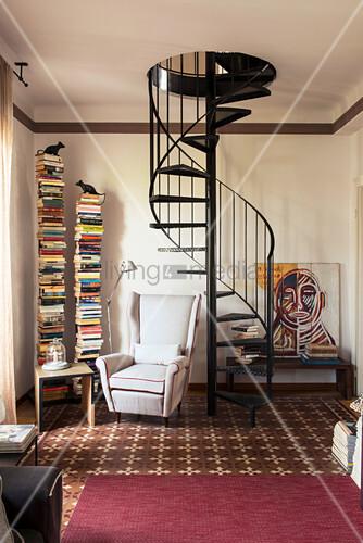 Leseecke mit vertikalen Regalen und Sessel neben der Wendeltreppe