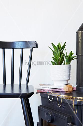 Schwarzer Sprossenstuhl neben Kaminofen mit modernem Schmuck