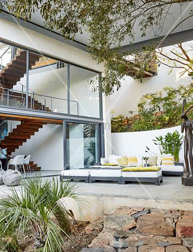 Polstermöbel auf der Terrasse vor einem Architektenhaus mit Glasfront