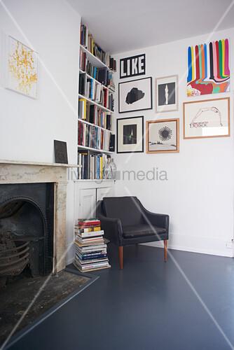 Sessel in der Ecke vor einem Bücherregal und Bilderwand