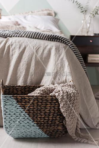 Diagonal bemalter Korb mit einem Strickplaid vor dem Bett