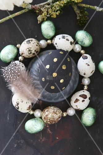 Schwarz-gold bemaltes Osterei in einem Kranz aus Wachteleiern