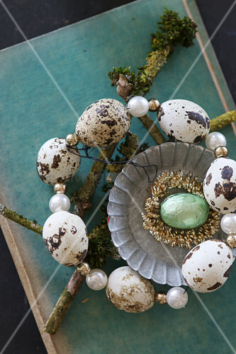 Circlet of threaded quail eggs around turquoise egg