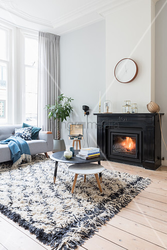 Coffee table on rug in front of fire in bright living room of period apartment
