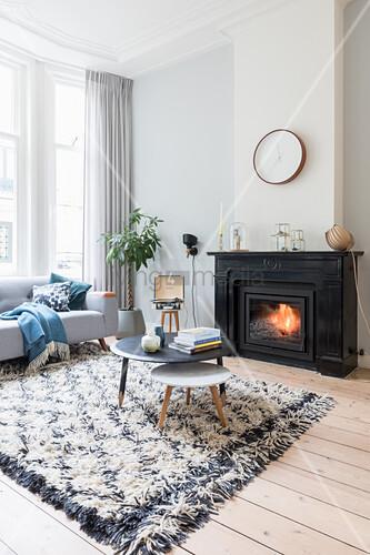 Coffeetable auf Teppich vor Kamin in hellem Altbau-Wohnzimmer