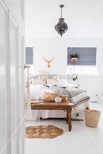 Blick auf Holztisch und Doppelbett in weißem Schlafzimmer
