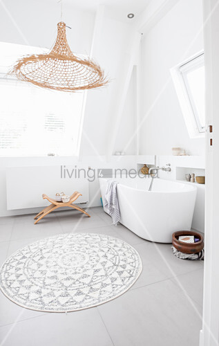 Free-standing bathtub and wicker lamp in bright bathroom