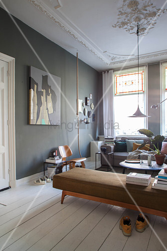 Books on retro couch, dark wall and white wooden floor in living room of period apartment