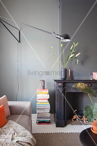 Sofa, Bücherstapel, Wandleuchte und stillgelegter Kamin im Altbau-Wohnzimmer mit dunkler Wand