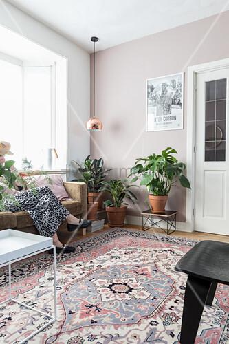 Zimmerpflanzen in hellem Wohnzimmer mit Teppich, Frau sitzt auf Sofa