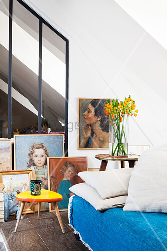 Paintings on floor leaning against glass and steel living room wall