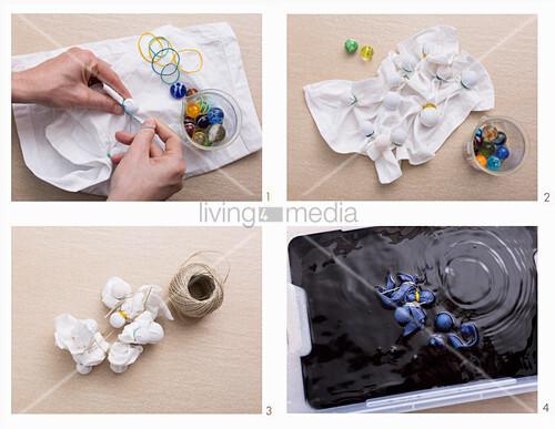 Tischset mit Shibori-Technik färben: Glasmurmeln mit Gummibändern auf dem Stoff fixieren, mit Band umwickeln und in die Farbe tauchen