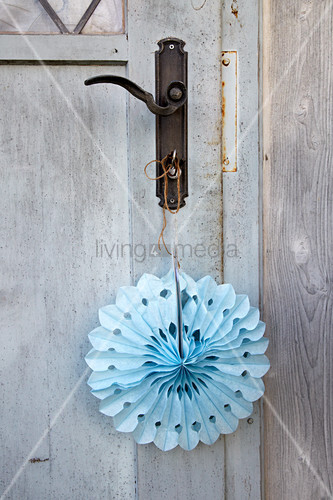 Handmade blue paper decoration hung from door
