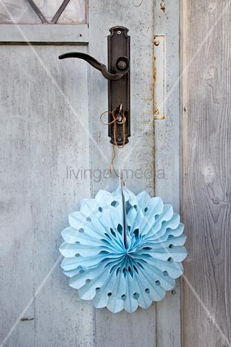 Selbstgebastelte Papierdeko in Blau an Tür hängend