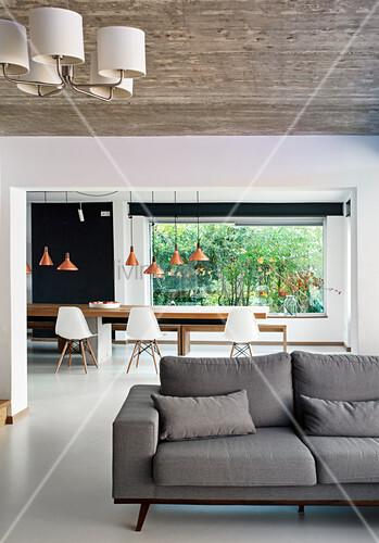Graues Sofa vor dem Durchgang zum Esszimmer mit weißem Boden