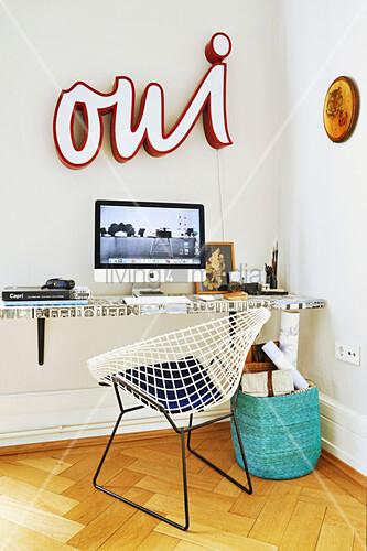 Monitor auf Schreibtisch mit tapezierter Tischplatte, Klassikerstuhl und Leuchtschrift an der Wand