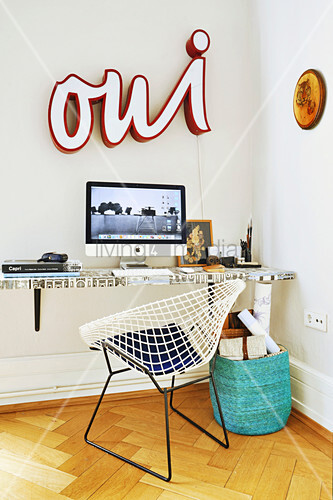 Monitor on desk with top covered in wallpaper, classic chair and illuminated word on wall