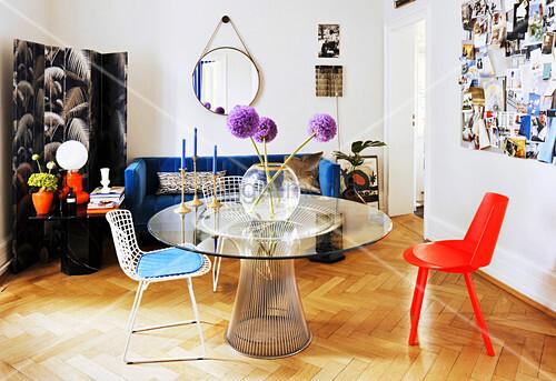 Metalltisch mit runder Glasplatte, verschiedene Stühle, Paravent und blaue Couch im Wohnzimmer