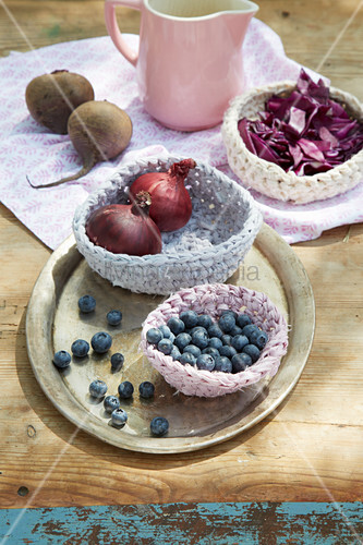 Blueberries and red onions in hand-crocheted basket made from dyed fabric strips