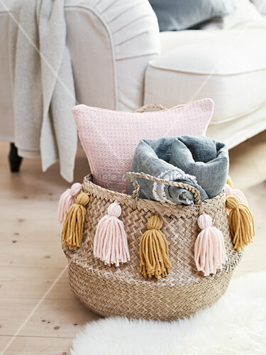 A basket for cushions and blankets decorated with DIY tassels