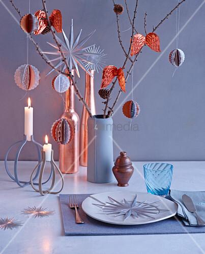 Weihnachtsgedeck und Tischdeko mit Kerzen, Zweigen und modernen Baumanhängern