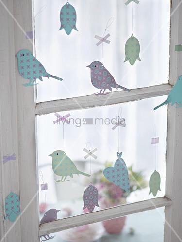 Metallanhänger am Fenster (Vögel, Blumen, Herzen) als Osterdeko