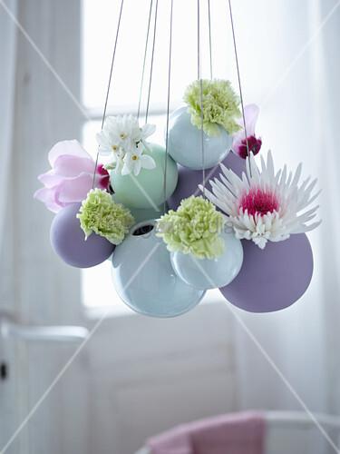 Kugel-Hängevasen mit Blumen als Osterdeko