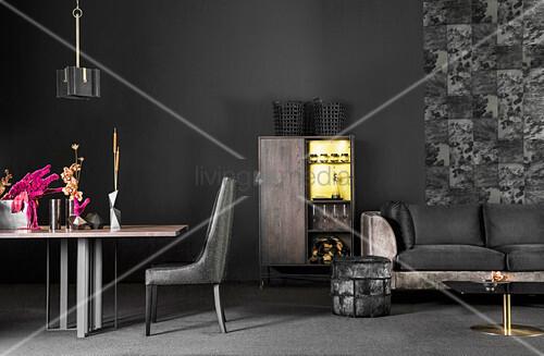 Sofa mit schwarzem Samtbezug, Hocker, Schrank und Esstisch mit Stuhl vor schwarzer Wand