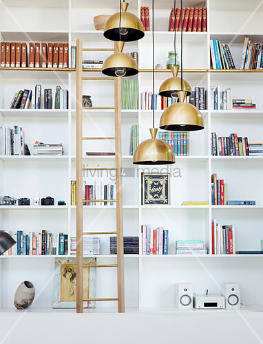 Library ladder and pendant lamps in front of white shelves
