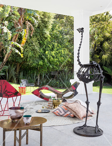 Designer furnishings and bird skeleton in seating area on roofed terrace