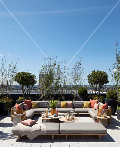 Large sofa combination and plants on roof terrace with view across London