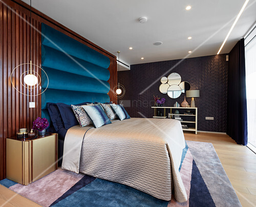 Glamorous bedroom in blue and metallic shades with various surface structures