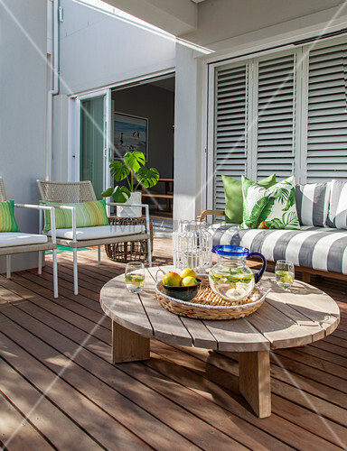 Round coffee table and sofa on terrace with wooden flooring