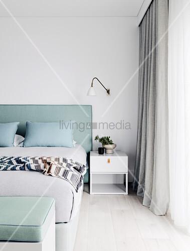Massgefertigtes Doppelbett mit mintgrünem Betthaupt, Nachttisch und Wandlampe im Schlafzimmer