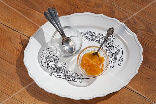 Schälchen mit Löffeln und Marmelade auf Teller mit Federmotiv