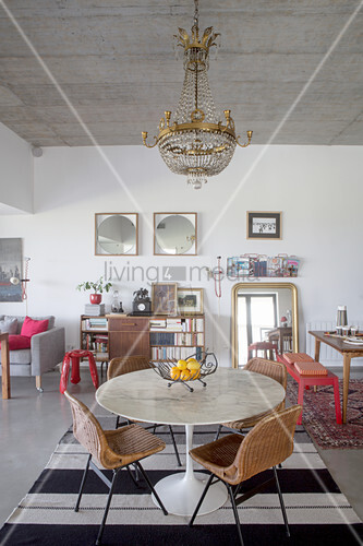 Round table and rattan chairs below chandelier in front of red bench, gilt-framed mirrors and bookcase